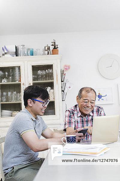 Son helping senior father paying bills at laptop