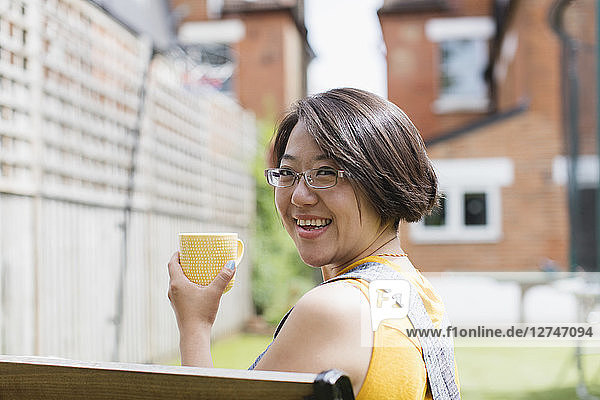 Portrait smiling woman drinking tea in sunny yard
