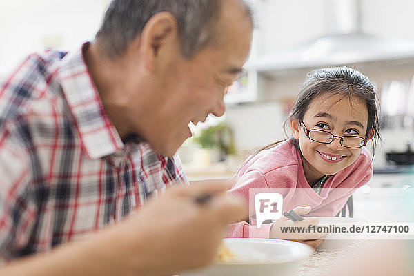 Smiling grandfather and granddaughter eating at table