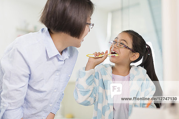 Mother watching daughter brushing teeth in bathroom