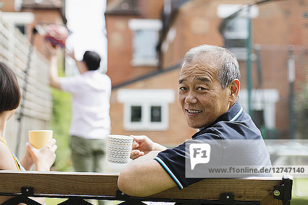 Portrait smiling senior man drinking tea with family in yard