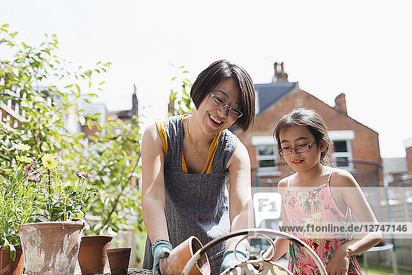 Mother and daughter gardening in sunny yard