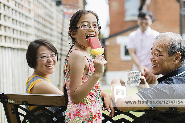 Portrait happy girl eating flavored ice with multi-generation family in back yard