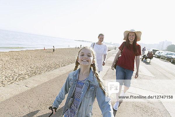 Portrait carefree girl on sunny beach boardwalk