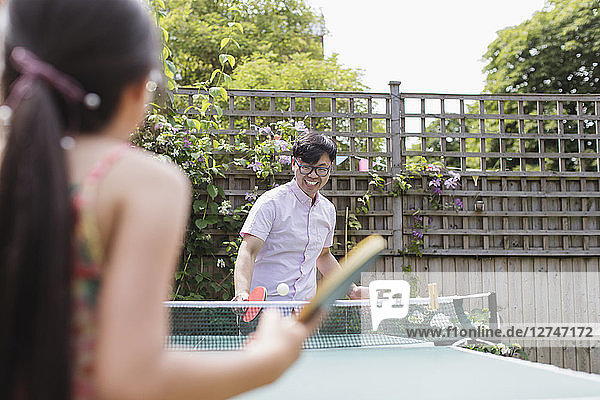 Father and daughter playing table tennis