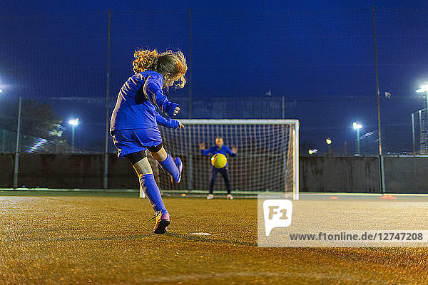 Girl soccer player kicking the ball toward goal