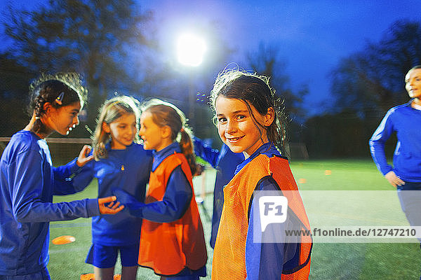 Portrait confident girl soccer player on field with team at night