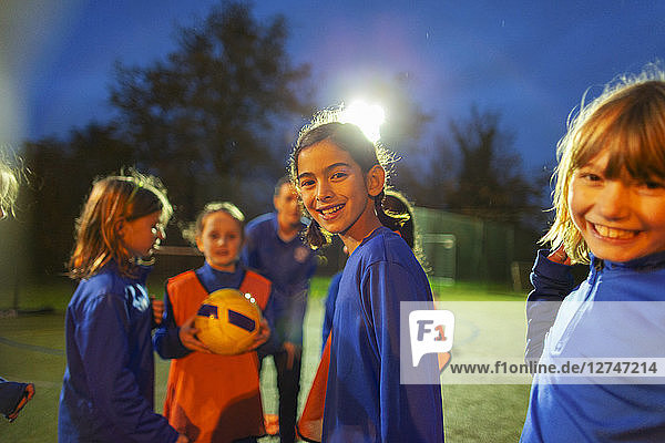 Portrait smiling girls soccer team on field at night