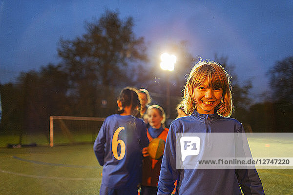 Portrait confident girl playing soccer with team on field at night