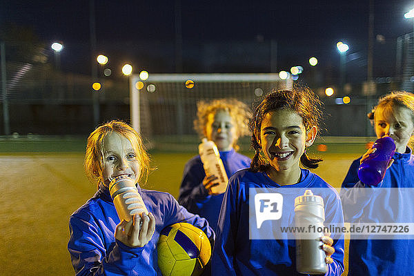 Portrait smiling girls soccer team taking a break from practice  drinking water on field at night
