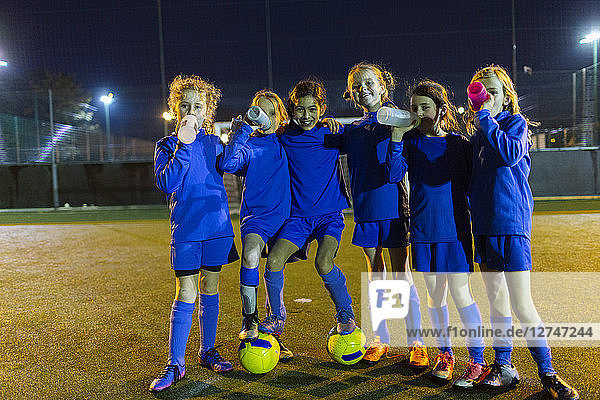 Portrait confident girls soccer team drinking water on field at night