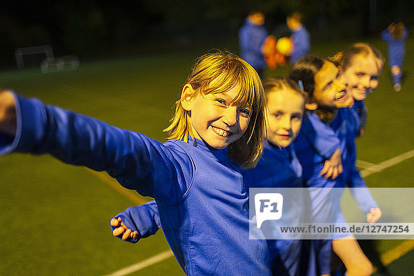 Portrait smiling  confident girls soccer team on field at night