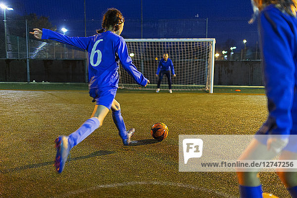 Girl soccer player kicking ball toward goal