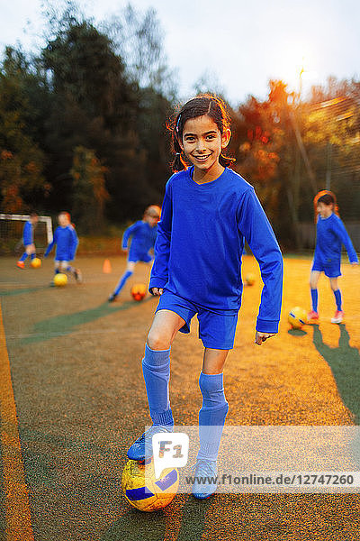 Portrait confident girl practicing soccer on field