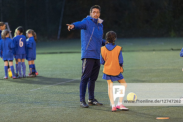 Soccer coach guiding girl soccer players practicing on field at night