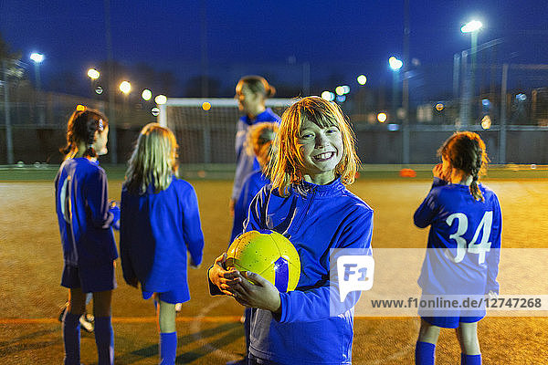 Portrait smiling  enthusiastic girl enjoying soccer practice on field at night