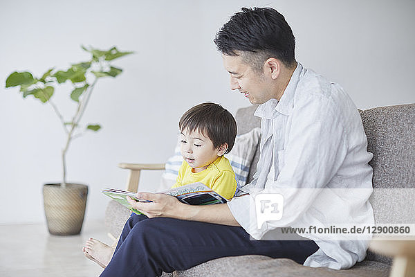 Japanese father and kid reading on the sofa