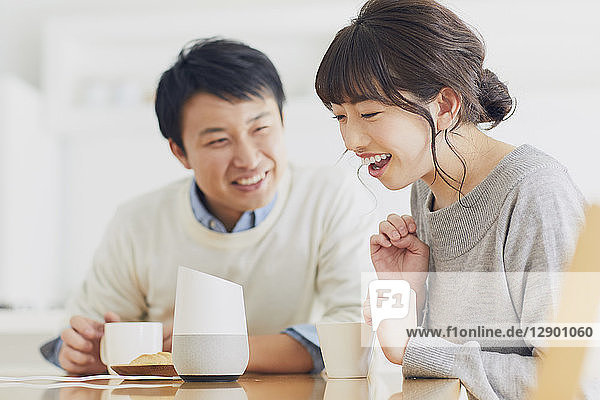 Japanese couple in the kitchen with smart home assistant