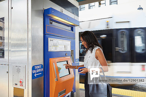 Geschäftsfrau kauft Zugfahrkarte am Automaten