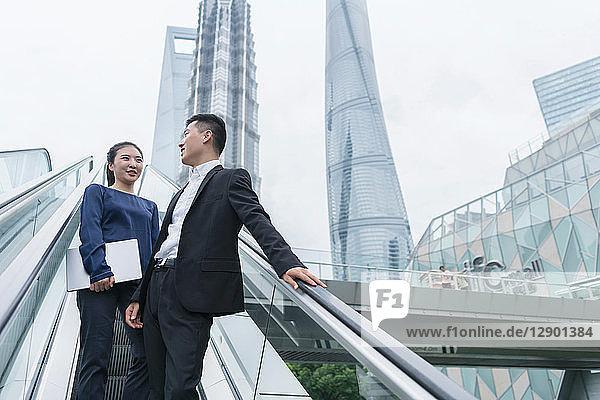 Junge Geschäftsfrau und Mann unterhalten sich beim Aufwärtsfahren auf der städtischen Rolltreppe  Shanghai  China