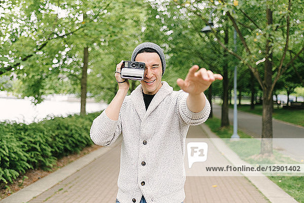 Young man taking photo with instant camera  Vancouver  Canada