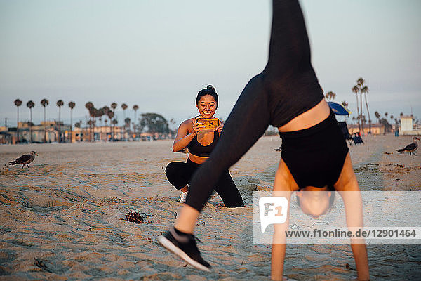 Friends photographing exercise on beach  Long Beach  California  US