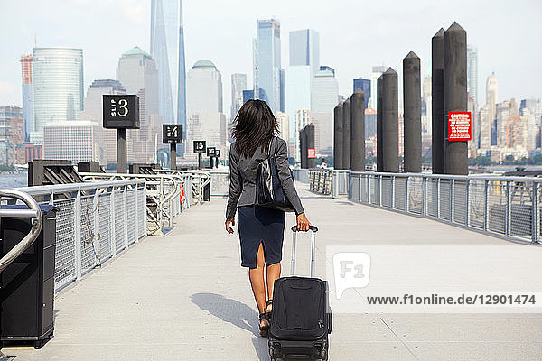 Businesswoman with wheeled luggage on ferry pier