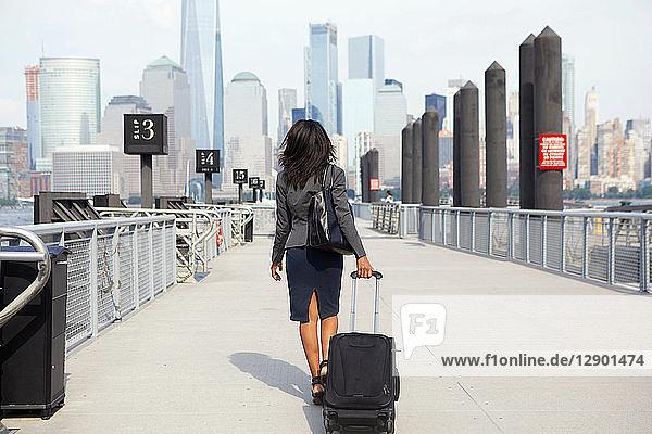 Geschäftsfrau mit Rollgepäck am Fähranleger