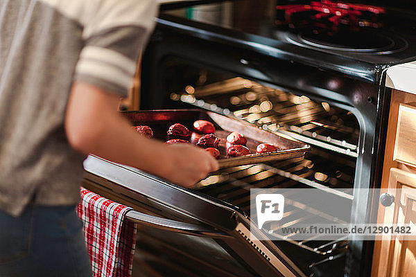 Girl placing tray of christmas cookies into oven  mid section