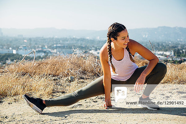 Woman doing stretching exercise on hilltop  Los Angeles  US