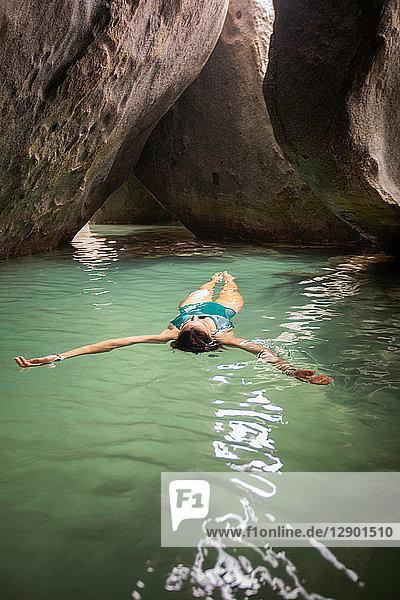 Junge Frau schwimmt auf dem Wasser in überfluteter Grotte  Virgin Gorda  Britische Jungferninseln