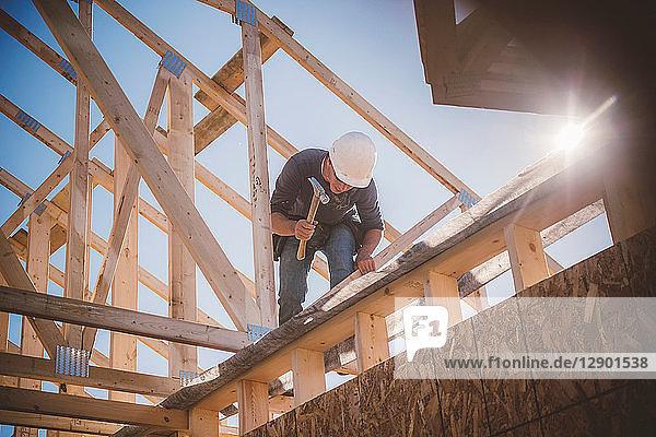Bauherr arbeitet am Dachstuhl eines Gebäudes