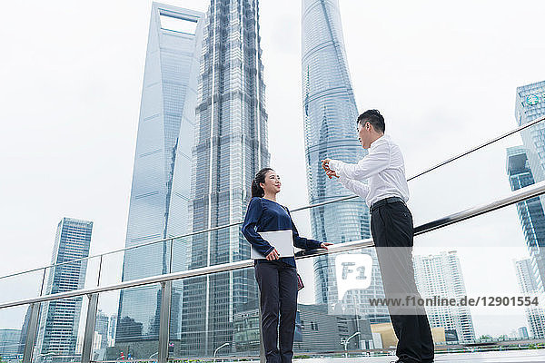 Young businesswoman and man talking in city financial district  Shanghai  China