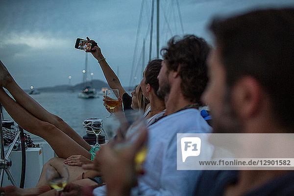 Vier Freunde sitzen in der Abenddämmerung auf dem Boot,  trinken Wein,  nehmen Selfie,  Britische Jungferninseln