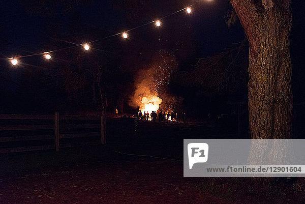 Silhouettenhafte Menschenmenge beobachtet nachts Lagerfeuer auf dem Feld