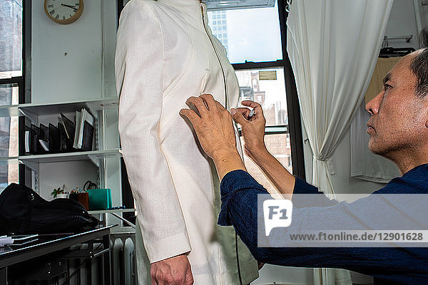 Passformmodell beim Anprobieren von maßgeschneiderten Jacken vor der Modenschau