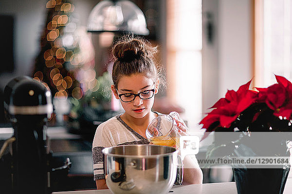 Girl pouring egg yolk into mixing bowl for christmas cookies at kitchen counter