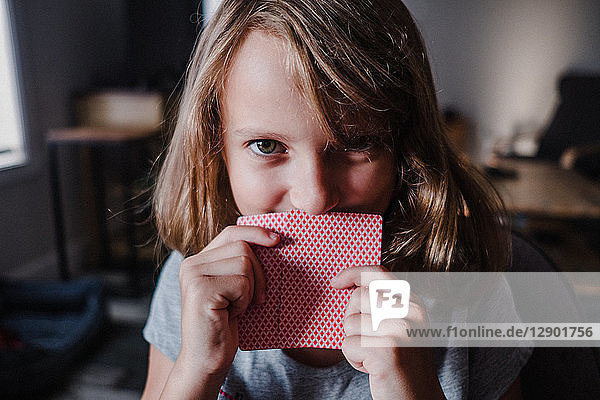 Girl hiding behind playing cards in living room  portrait