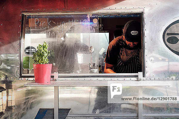 Man cooking in camper van food truck