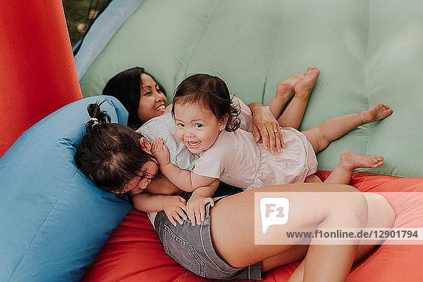 Mutter und Töchter spielen auf der Hüpfburg