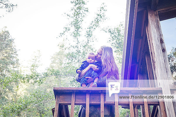 Mother with baby son on balcony of wooden house in forest  Cazadero  California  USA