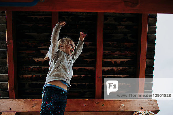 Girl jumping with arms raised on playground platform