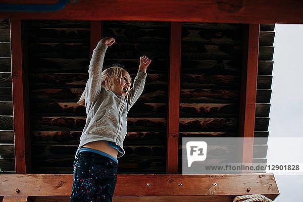 Mädchen springt mit erhobenen Armen auf Spielplatzplattform