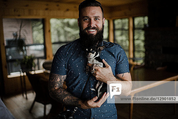 Young man holding pet dog in living room  portrait