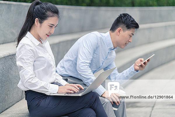 Junge Geschäftsfrau und junger Geschäftsmann mit Laptop und Blick auf Smartphone am Stadtsitz  Shanghai  China