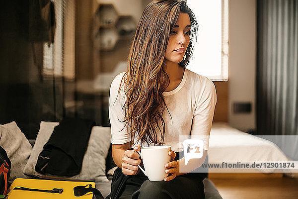 Frau mit Tasse beim Nachdenken im Schlafzimmer