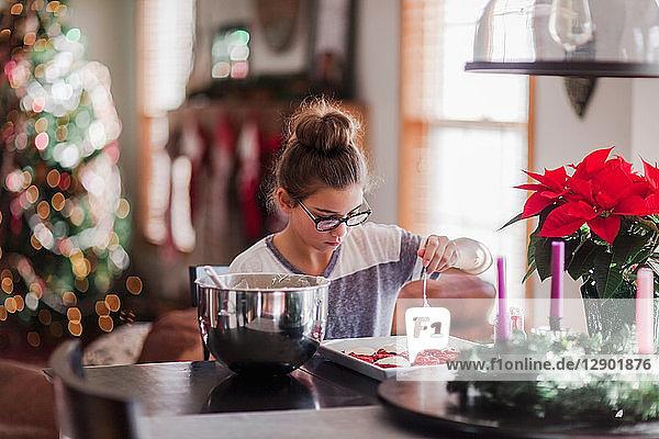 Mädchen glasieren Weihnachtsplätzchen