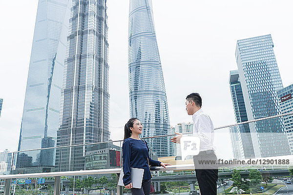Junge Geschäftsfrau und Mann unterhalten sich im Finanzbezirk der Stadt  Shanghai  China