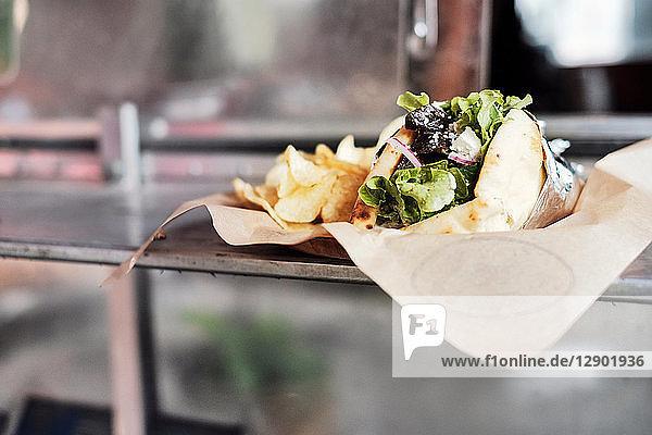 Mahlzeit mit Salatwickel und Kartoffelchips auf der Theke