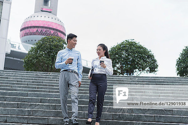 Junge Geschäftsfrau und Mann mit Kaffee zum Mitnehmen bewegen sich die Stadttreppe hinunter  Shanghai  China